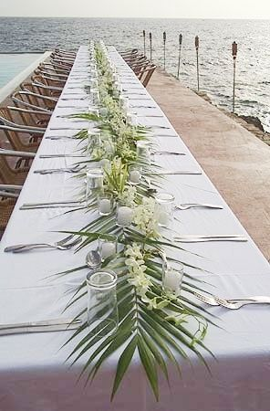 Palm Leaves on Tables with scattered orchids. for your beach reception