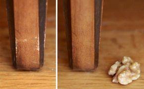 Rubbele mit einer Walnuss über beschädigte Stellen an Holzmöbeln.