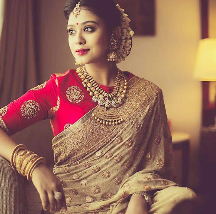 Gold jewelry, silk sari and blouse, and fresh jasmines in hair - a quintessential indian bride.