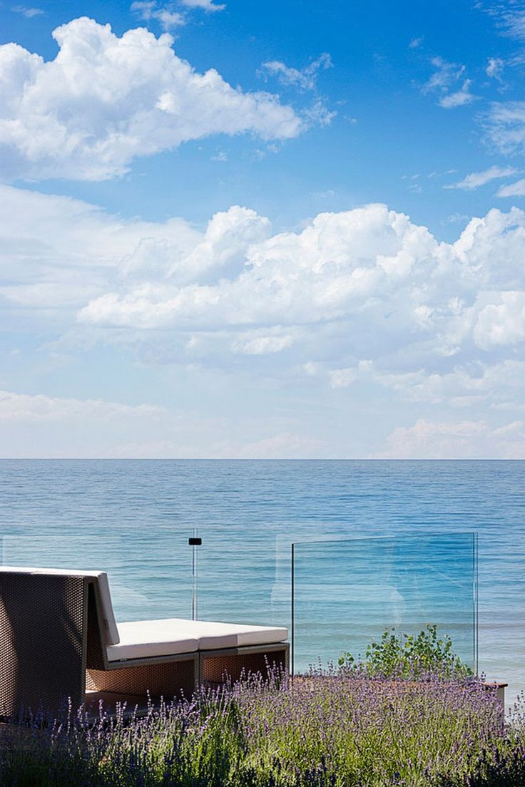 Cozy Daybed On Wooden Deck By The Pool Side With Tempered Glass Balustrade Design And Plants Facing To The Blue Beach Scenery Curved Architecture of the Big House On The Beach Home design
