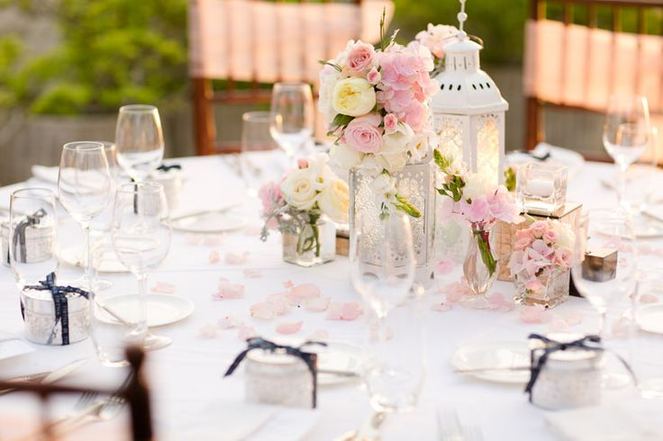 Centerpiece of White lanterns adorned with Hydrangea, Rose, Garden Rose, Lisianthus and Foliage c