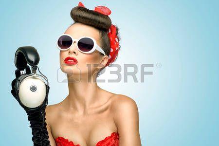 acconciature: La foto retrò di una ragazza carina pin-up in occhiali da sole con le cuffie musicali d'epoca