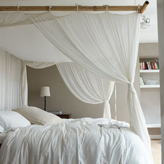 Four-poster bed with white canopy curtains, bedside table, light and shelving.