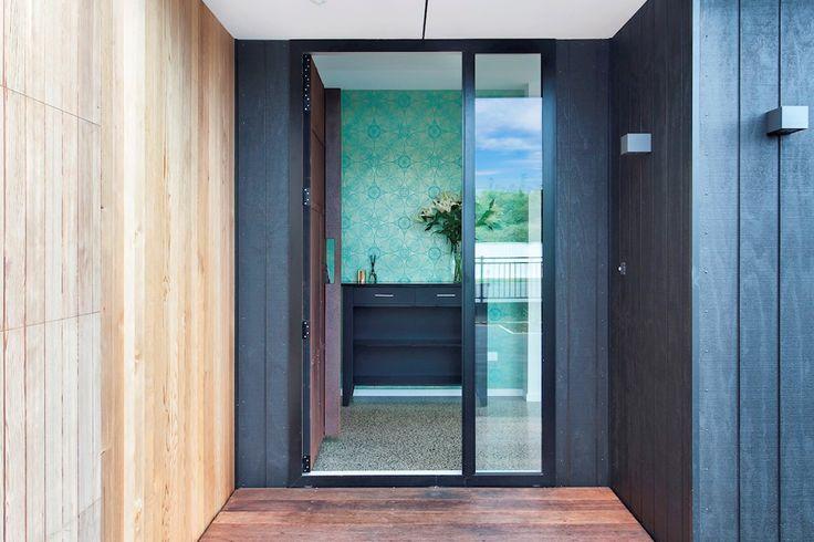 Corten steel door, vertical black cedar cladding against jade green entrance way.