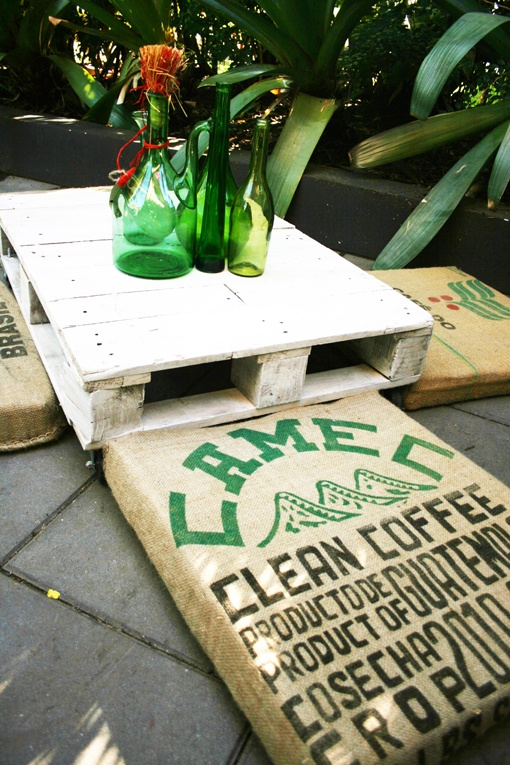 Coffee bean bag floor cushions matched with repurposed packing palette with casters and vintage green bottles.