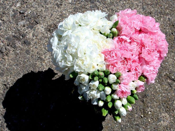 Mini claveles en florero de vidrio reciclado forma de corazón.