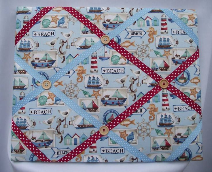 """This handmade fabric memo board is made from a lightly padded artist canvas and covered in a lovely seaside theme fabrc. The grosgrain ribbon is in complimentary colours to match the fabric. The back of the memo board is also finished with calico fabric for a neat finish.  I also include eyelets and natural jute string for hanging.  Measures 20"""" x 16"""" (50.5cm x 40.5cm)  PRICE: £14.99 + P&P"""