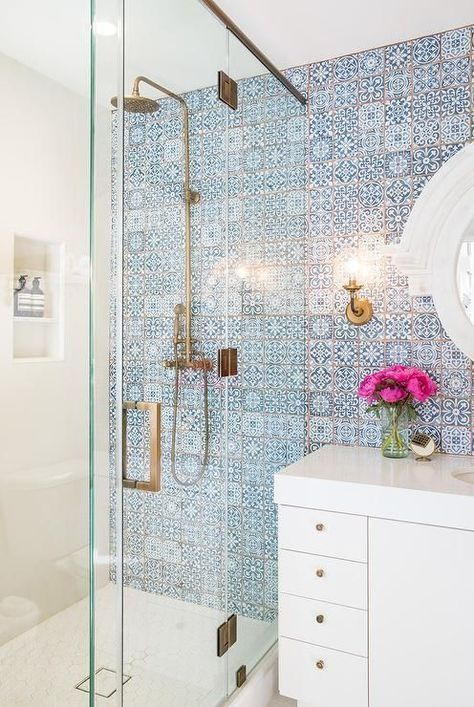 blue and white bathroom tile with golden shower head and white vanity/sink area