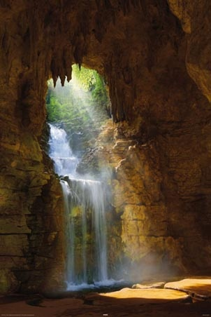Spectacular scene of a sparkling waterfall flowing over fresh green plant life through an opening to a magnificent stone cave, & made all the more enchanting by beautiful golden sunbeams reaching through!