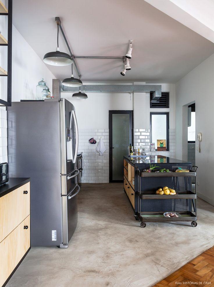 cozinha integrada de estilo industrial com piso de cimento queimado e subway tiles nas paredes