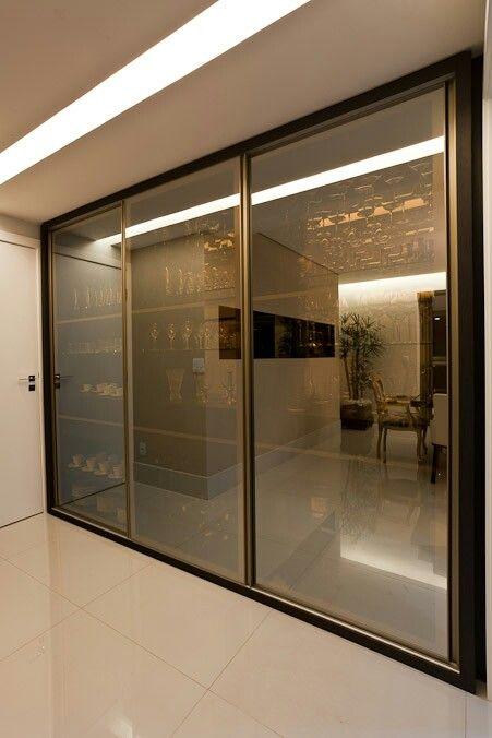 Sheila Mundim Arquitetura e Design de interiores - Cristaleira com portas de correr com vidro refletivo bronze.