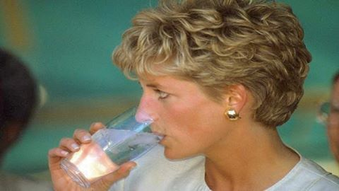 12 July 1993: Princess Diana drinks a glass of water during her visit to Nemazura Feeding Centre, a Red Cross project for refugees in Mazera, Zimbabwe.