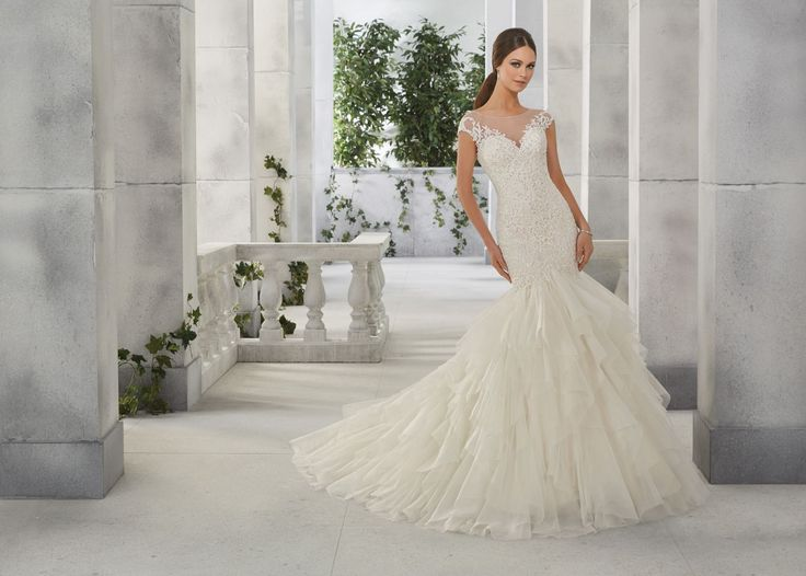 FUMIKO Dopasowana suknia ślubna z falbanami Madeline Gardner Szykowna suknia ślubna w kształcie rybki, z tiulową spódnicą, pokrytą falbanami. Góra …
