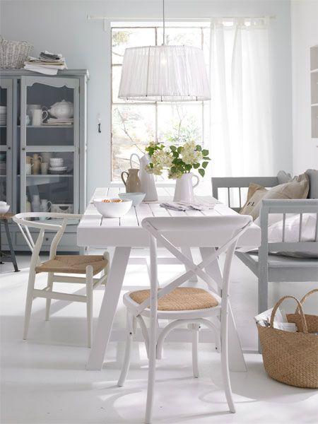 Białe krzesła z drewna gietego i drewniana ławka w stylu skandynawskim przy stole w jadalni