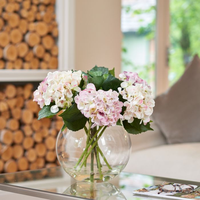 We love our Fishbowl arrangements here at Peony, and this one is no exception. A total of six beautiful Hydrangeas in soft pastel shades of cream, pink and lavender tastefully adorn this large fishbowl. We take every detail of nature in to account when creating our faux flower Hydrangeas. From the delicate flower heads to the gentle graduation of colour, we try to ensure our stems are botanically correct in every way. Set in Still Water™, this magnificent arrangement would be most fitting as…