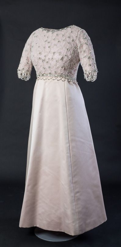 """Silk satin dress with beaded embroidery designed by Hardy Amies for HM The Queen, 1972.   This dress was worn by HM The Queen for her state visit to France in 1972. It was also worn in the official photograph taken to celebrate her Silver Jubilee in 1977. This image was widely reproduced on many commemorative items. It was also used by Andy Warhol for his screen prints """"Reigning Queens"""" in 1985 and by the Sex Pistols on their """"God Save the Queen"""" album cover."""