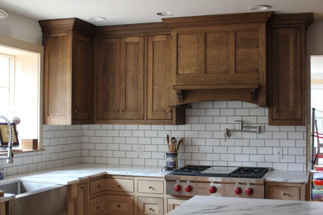 dark grout white tiles with oak cabinets