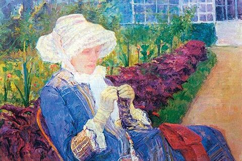 Woman in a lace bonnet sits tatting or knitting in a garden with rows of flowers