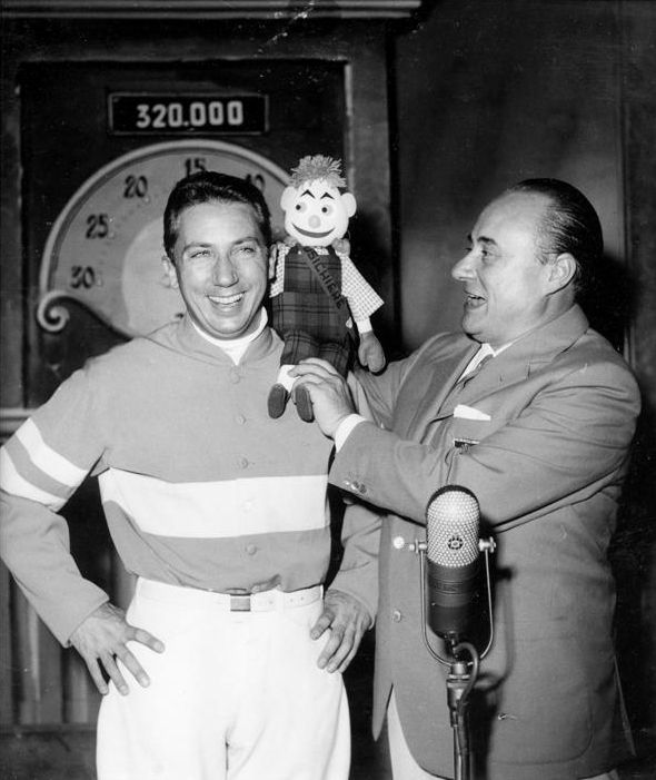 "Popular Italian-American TV and radio presenter Mike Bongiorno, carrying on his shoulder the mascotte of ""Il Musichiere"", and Mario Riva."