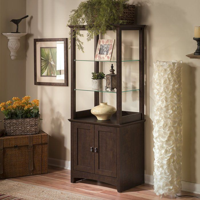 Tastefully display objects, art or unique works with style and flair. The Tall Library Storage Cabinet holds books, personal items or displays of all kinds. Two attractive, adjustable clear tempered glass shelves fit most room decor. Spacious bottom shelf is adjustable and enclosed by two doors with Aged metal door hardware. Works at home as a curio cabinet or in an office as a combination bookshelf and storage unit. Small footprint allows room-placement flexibility. Solidly constructed and…