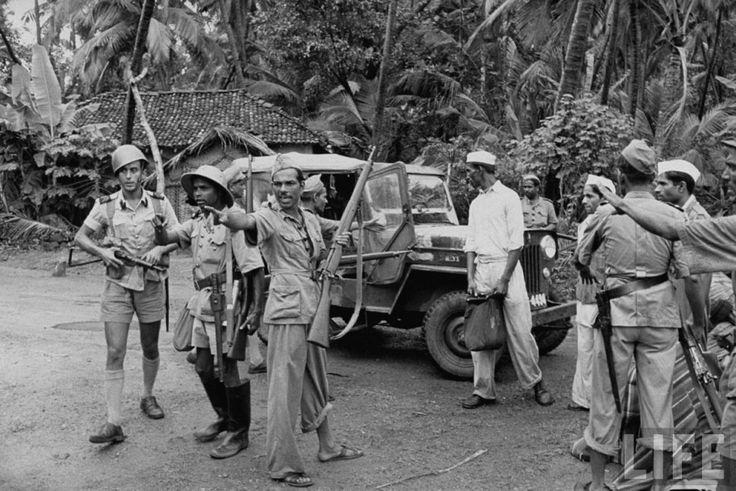 """En uno de los numerosos incidentes fronterizos, fuerzas policiales y militares portuguesas disuelven una """"marcha pacífica"""" sobra Goa. Los """"satyagrahis"""", vestidos de blanco, muestran el contenido  de sus bolsas antes de ser transportados en vehículos militares y autobuses civiles hasta los destacamentos de policía convertidos en centros de detención (fotografía publicada –ca. 1954– por la revista Life - See more at…"""