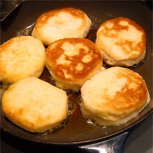 """butter for frying  1 can refrigerated biscuits.  Peel each biscuit into two halves. Place each half on the griddle. Fry until the biscuit is golden brown - you'll see the """"cooked"""" just at the very edge of the bottom of the biscuit. Flip and fry the other side. (If you don't pull them into halves, they'll end up gooey inside.)"""