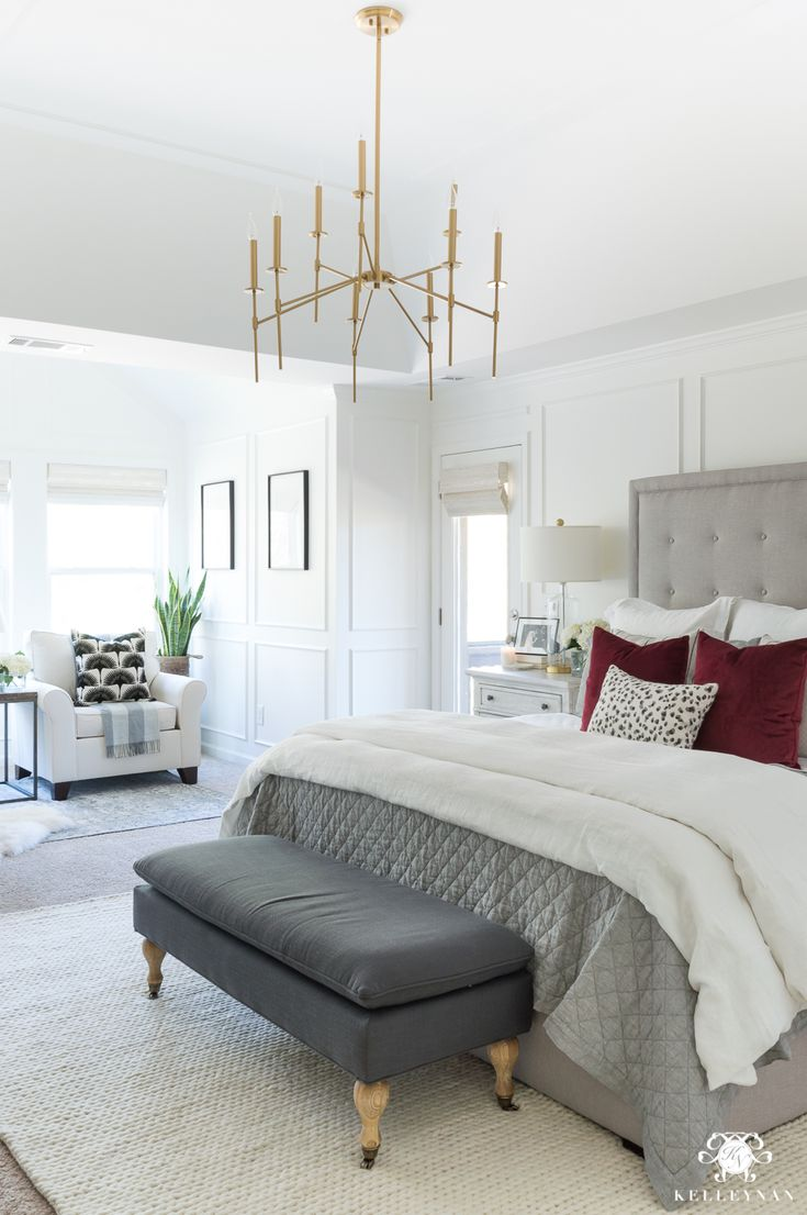 Master bedroom decorating ideas with modern brass chandelier and white walls with molding