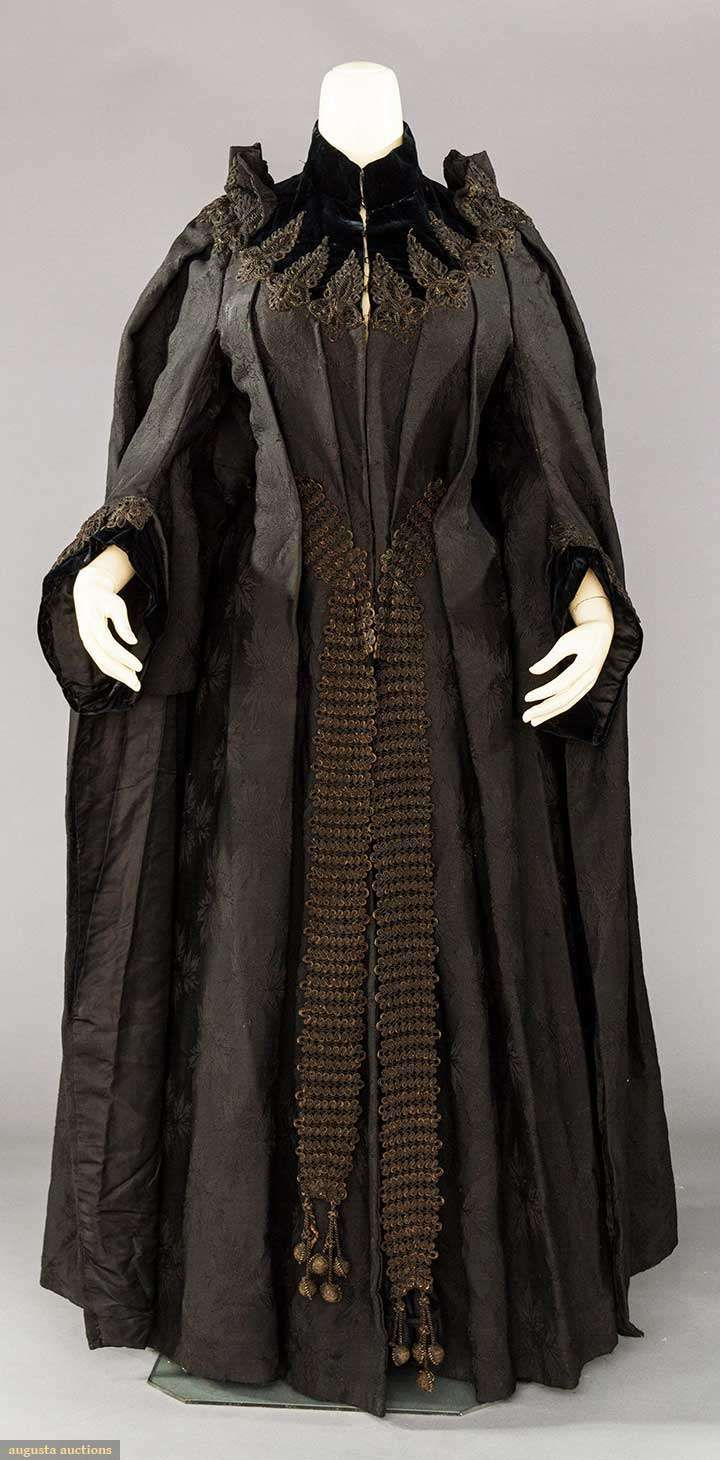 """WOOL DOLMAN BUSTLE COAT, PARIS, MID 1880s  Black wool leaf patterned damask, cuffs & yoke of black velvet w/ black cord appliques, label """"Cacard & Raffin"""", knife pleats to CF & CB, large CB applique anchors back pleats, long corded CF bands w/ ball tasseled ends, black silk twill lining, W 30"""", L 53"""" (front view)"""