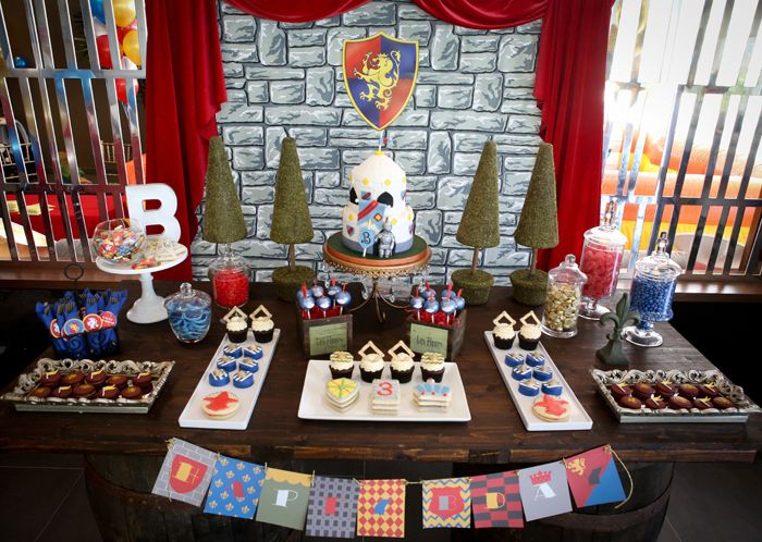 Brave Knight Inspired Party for Boys |the dessert table look like the front of a castle with the fortress print backdrop, red velvet curtains and vertical cone topiaries.