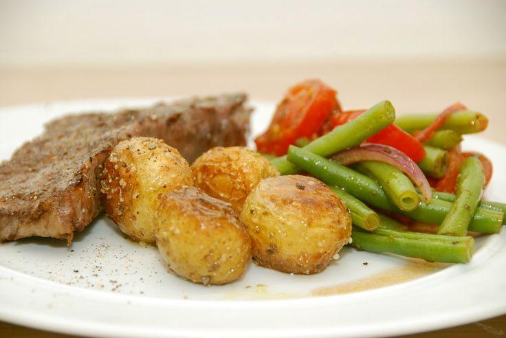 Varm bønnesalat er lækkert tilbehør til retter med kød, hvor du bager grønne bønner, tomater og lidt hvidløg kort tid i ovnen. Smages til med oregano. Foto: Guffeliguf.dk.