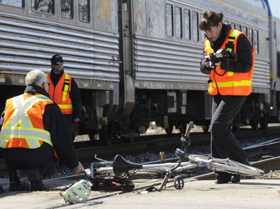 Police investigate the scene of a collision between a train and cyclist on Thursday in Kitchener.