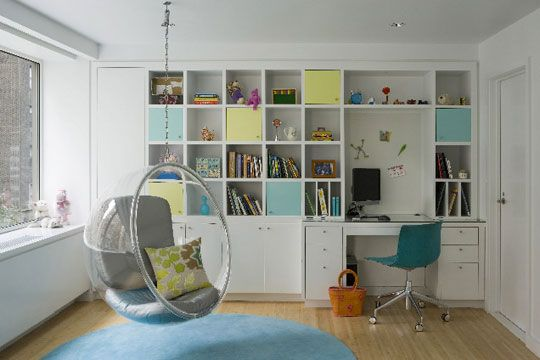 A light-filled study where everything has a place on neat square shelves and behind pale eggshell blue and lemon yellow doors. The hanging Adelta bubble chair is the key piece that gives the room a fanciful lift.