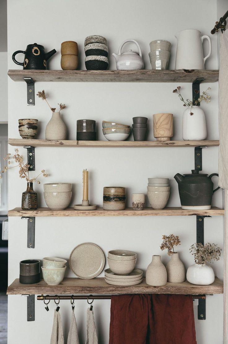 Eine handgefertigte Wabi Sabi-Keramik auf rohen, kantigen Regalen schafft einen einfachen, aber schönen, modernen rustikalen Küchen-Look