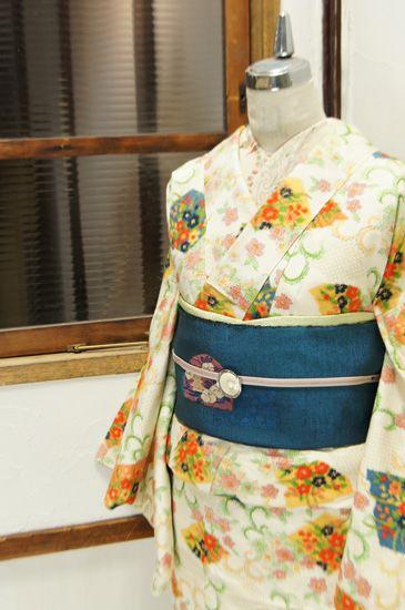 優しい白の地に、花寄せる色とりどりの色紙と優美な唐草文様が織り出された正絹紬の袷着物です。
