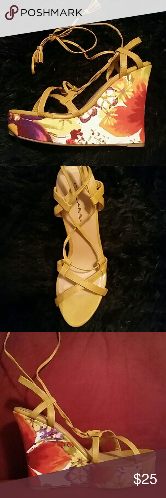 Beautiful gold flower design wedge heels Gold wedge heel sandals with orange flower designs on the heels. Shoes have the fashionable new tie up design. 5 inch heel with a 1.5 in platform. Never worn. Shoes Wedges