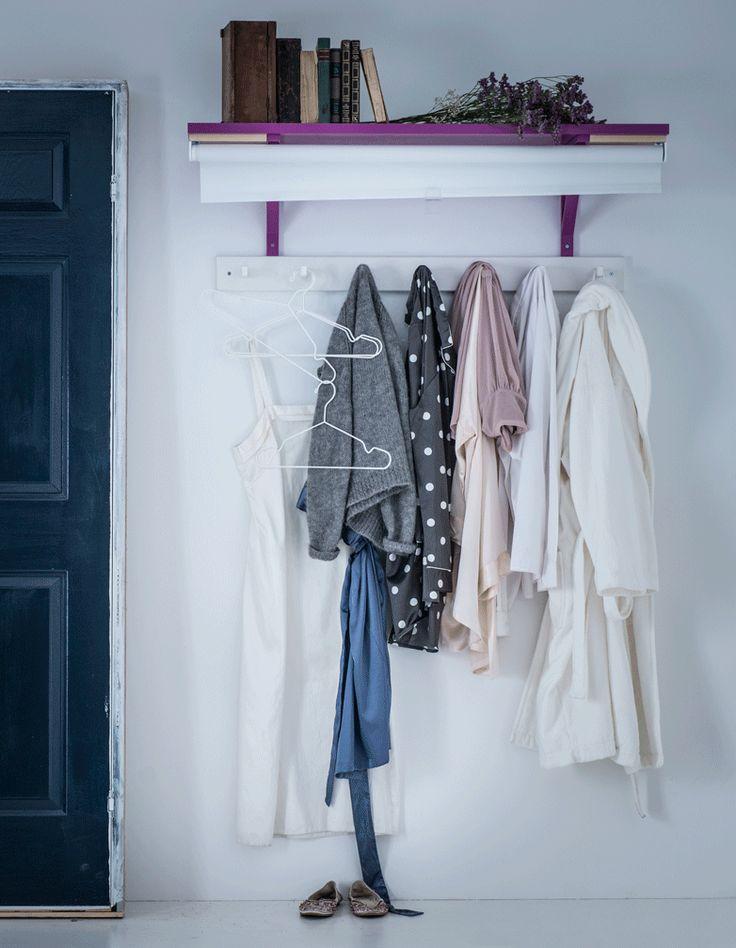 Les vêtements sont suspendus à des crochets fixés au mur sous une tablette et cachés par un store occultant TUPPLUR décoré à la main.