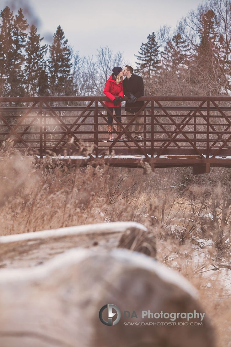 A kiss on the bridge in winter - Winter Engagement photo shoot by DA Photography, www.daphotostudio.com