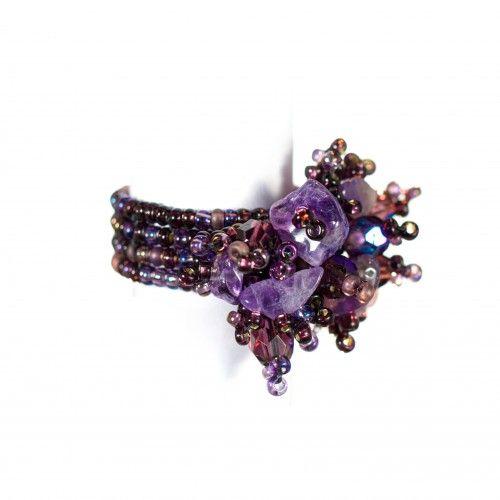 89 kronor på masomenos.se: en glad lila ring som sticker ut, knuten för hand med hundratals funkiga plastpärlor. På ovansidan exploderar pärlorna i en bukett av fasetter, glas och stenar i olika form och nyans.