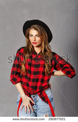 Young sexy woman in a hat, plaid shirt and jeans posing in studio, look at the camera. Girl hipstor. The concept of modern fashion. @shutterstock