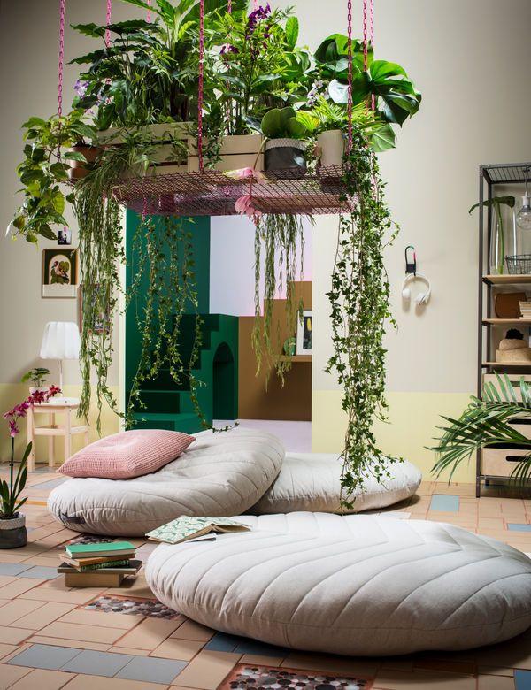 Stue med 3 store gulvpuder med beige betræk. I loftet hænger en hylde med masser af grønne planter.