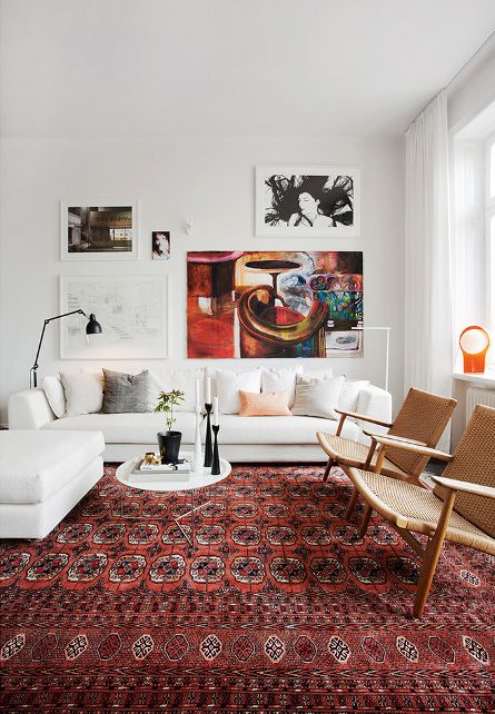 warm cozy living room with oriental rug white sofa danish modern chairs gallery art wall