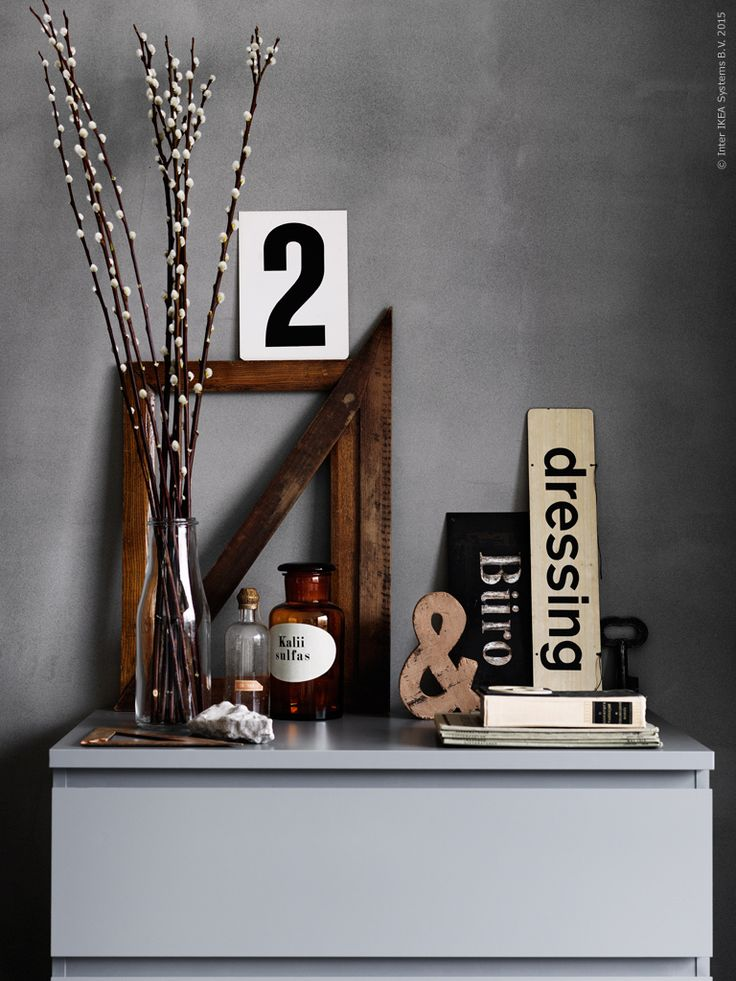 MALM byrå med tre lådor i en sober grå nyans. Vi kombinerar gråskalan med ett stilleben av udda gamla träföremål och grafiska skyltar. Vårens första videkvistar i ENSIDIG vas.