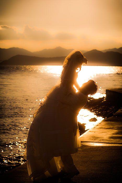 夕焼けと海を背にふたりを写したロケーションフォト。最高にロマンチックな組み合わせでのロケーション撮影で、ふたりの夢が叶った瞬間です。兵庫県淡路島で洋装結婚写真のロケーション撮影。