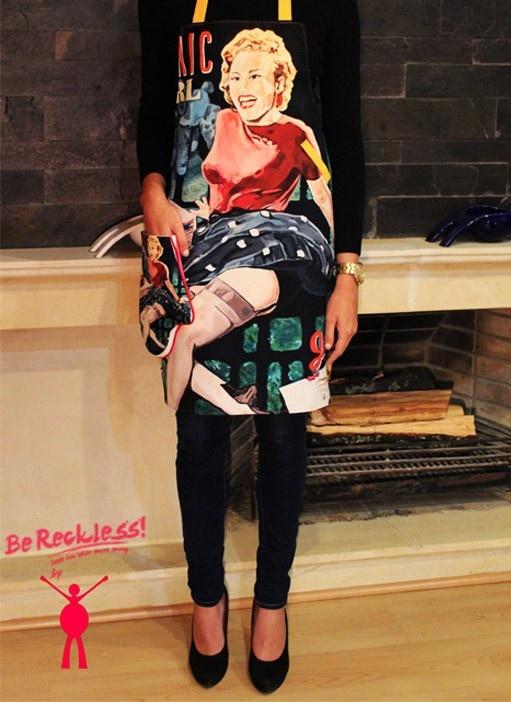 """Delantal de cocina enterizo marca Sfido. Se imprime una réplica exclusiva de la obra """"atomic girl"""" (con tendencia Pop Art) de la artista colombiana Karen Cáceres. Nuestros productos son exclusivos, ya que el número de copias por cada referencia y obra es controlado y reducido."""