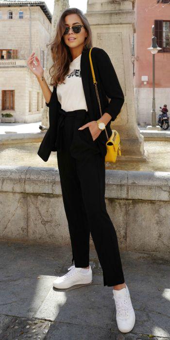 Kenza Zouiten + slick black cigarette trouser tied at the waist + white graphic tee + black cardi + spring look + bright white sneakers + miniature yellow handbag.   Blazer/Trousers/Tee: Gina Tricot.