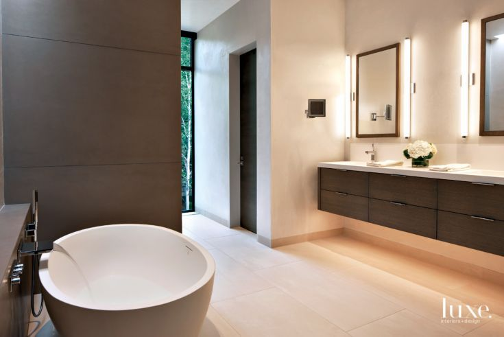 Floor tiles by Mosa and a floating vanity continue the structure's streamlined feel into the spacious master bathroom. A Tyrrell & Laing International tub pairs with a tub filler by Dornbracht.