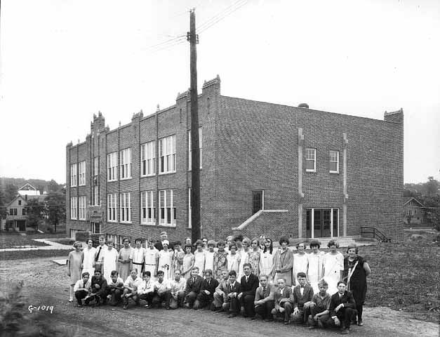 School group at Murray School, St. Paul, ca. 1925.  In 1925, a new school was built at Buford and Grantham with 13 classrooms and a gym and the Murray name was transferred to the school. Grades K-3 and 7-9 moved to the Buford site; grades 4-6 remained at the Como Avenue school which was renamed Guttersen School, after Gilbert Guttersen, a prominent local businessman in St. Anthony Park.