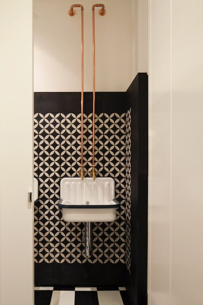 Exposed copper pipes and industrial-style basins in the bathroom