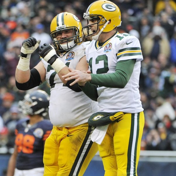 Green Bay quarterback Aaron Rodgers celebrates one of his three touchdown passes to James Jones with lineman Josh Sitton as the Packers  clinch the NFC North title.