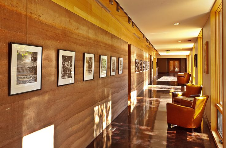 Dappled sunlight filters through trees creating a softer, warmer late afternoon ambiance within this quiet corridor | Sublette County Library – SIREWALL | Structural Insulated Rammed Earth
